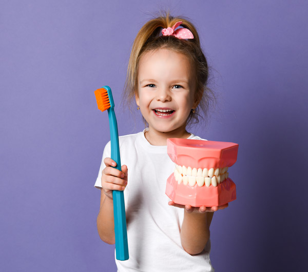 Laughing kid girl shows us big dental implant model and giant to