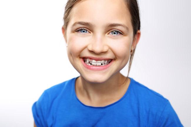 Dziecko w aparaciku ortodontycznym, sposób na proste zęby i pi