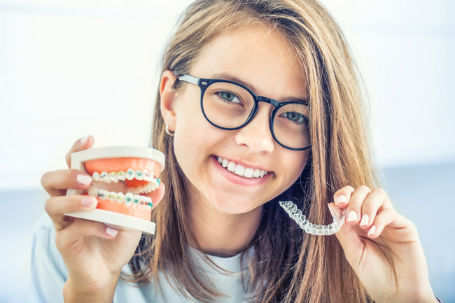 Dental invisible braces or silicone trainer in the hands of a young smiling girl. Orthodontic concept - Invisalign.